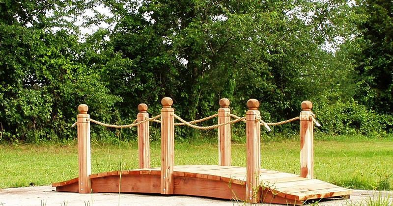 Wooden bridge garden feature with side rails