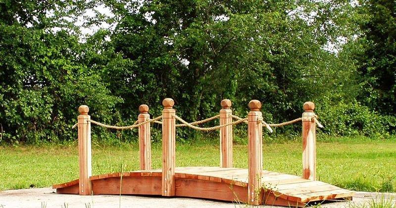 Wooden bridge garden feature with side rails